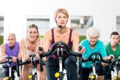 转动在健身的健身房的资深人骑自行车 免版税图库摄影