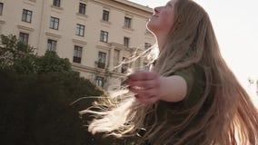 转动在城市广场的绿色礼服的年轻人相当狡猾的女孩 股票录像