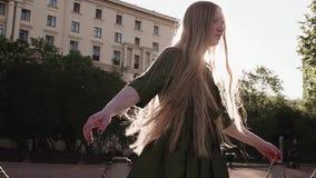 转动在城市广场的绿色礼服的年轻俏丽的姜女孩 股票视频