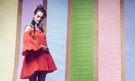 转动在多背景的橙色礼服的俏丽的妇女 免版税图库摄影