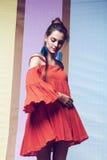 转动在多背景的橙色礼服的妇女 免版税库存图片