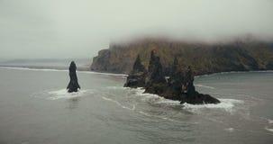 转动在拖钓附近的直升机在冰岛用脚尖踢在海的峭壁 美丽的黑火山的海滩和山在雾 影视素材