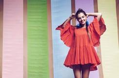 转动在有大袖子的橙色礼服的快乐的妇女 免版税库存照片