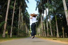 转动在棕榈树之间的女孩 免版税库存照片