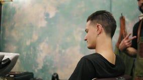 转动在椅子附近的年轻有胡子的理发师,当有刺穿的时髦的客户在他的耳朵和tatoo坐时 股票视频