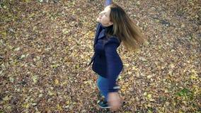 转动在秋天公园慢动作的落叶中的美女 4k 60fps 外套的女孩走在的 股票录像