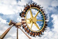 转动在美丽的多云天空的黄色公园轮子 免版税库存照片