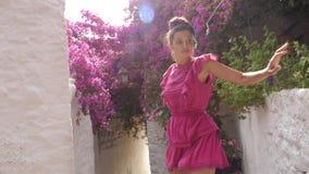 转动在街道上的一个短的桃红色礼服身分的女孩在老镇 股票视频