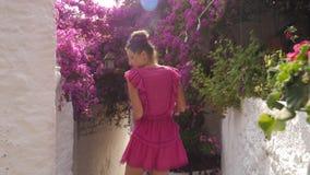 转动在街道上的一个短的桃红色礼服身分的女孩在老镇 股票录像