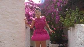 转动在街道上的一个短的桃红色礼服身分的女孩在老镇 影视素材