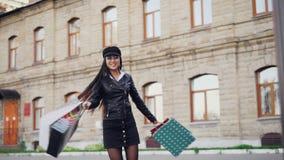 转动在街道的愉快的亚裔妇女慢动作画象拿着礼物在天购物以后请求 正 股票视频