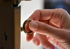 转动在门的妇女的手一把钥匙 库存照片