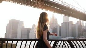 转动在风景日落河堤防的美丽的愉快的白种人女孩在布鲁克林大桥,纽约附近慢动作 影视素材