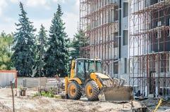 转动地球搬家工人或装载者工业机械在新的居民住房建造场所有脚手架的 图库摄影