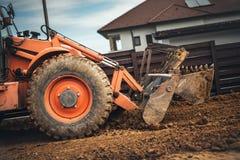 转动完成在站点的装载者挖掘机建筑工作 免版税图库摄影