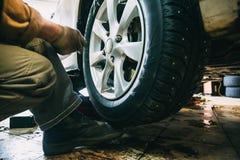 转动平衡或修理并且改变车胎在自动服务车库或车间由技工 免版税库存照片