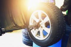 转动平衡或修理并且改变车胎在自动服务车库或车间由技工 免版税库存图片