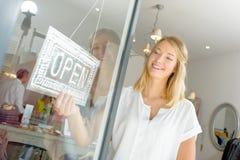 转动开放和闭合的标志的商店工作者 免版税图库摄影
