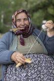 转动棉花的年长妇女 免版税库存图片