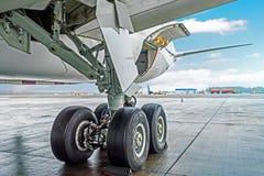 转动橡胶轮胎后方起落架机架飞机航空器,在翼视图下 库存图片