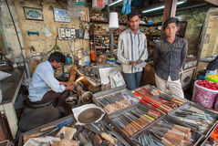 转动的商店和刀子商店的工作者在农贸市场上 免版税库存照片