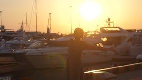 转动的礼服的年轻俏丽的妇女跳舞在日落海船、游艇和透镜火光作用反对 影视素材