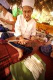 转动羊毛的年长妇女的手 库存照片