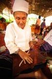 转动羊毛的年长妇女的手 免版税库存图片