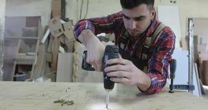 转动自动攻丝螺杆的一位年轻木匠与螺丝刀在家具生产 股票视频