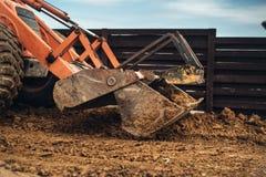 转动装载者挖掘机,反向铲装载者运作在建造场所的机械细节 免版税库存图片