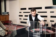 转动轮盘赌的赌博娱乐场经销商 免版税库存照片