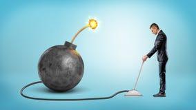 转动金属杠杆的小商人连接到一颗大铁炸弹用一根被点燃的保险丝 图库摄影
