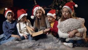 转动页的逗人喜爱的孩子,当看书在屋子里与圣诞装饰时 股票录像