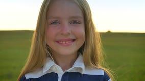 转动顶头往照相机和微笑,逗人喜爱的愉快的孩子与蓝眼睛的美丽的矮小的白肤金发的女孩站立在麦子 股票录像