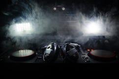转动,混合和抓在夜总会的DJ, dj的手扭捏在dj的甲板、闪光灯光和雾的各种各样的轨道控制, 免版税库存图片