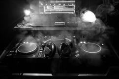 转动,混合和抓在夜总会的DJ, dj的手扭捏在dj的甲板、闪光灯光和雾的各种各样的轨道控制, 免版税库存照片