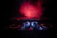 转动,混合和抓在夜总会的DJ, dj的手扭捏在dj的甲板、闪光灯光和雾的各种各样的轨道控制, 免版税图库摄影