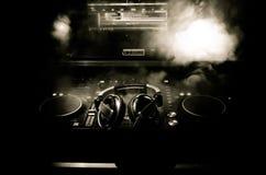 转动,混合和抓在夜总会的DJ, dj的手扭捏在dj的甲板、闪光灯光和雾的各种各样的轨道控制, 库存照片