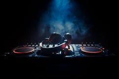 转动,混合和抓在夜总会的DJ, dj的手扭捏在dj的甲板、闪光灯光和雾的各种各样的轨道控制 免版税库存照片