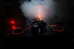 转动,混合和抓在夜总会的DJ, dj的手扭捏在dj的甲板、闪光灯光和雾的各种各样的轨道控制 免版税图库摄影