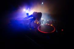 转动,混合和抓在夜总会的DJ, dj的手扭捏在dj的甲板、闪光灯光和雾的各种各样的轨道控制 库存照片