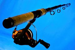 转动-钓鱼的体育滑车在蓝色背景的诱饵 转动容易在长的熔铸的诱剂的水身体和 免版税图库摄影