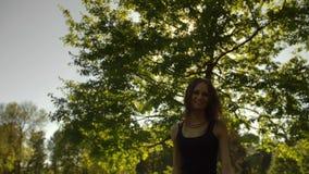 转向一台照相机的可爱的少妇在公园 影视素材