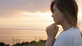 转向上帝的年轻美女本质上,女孩祈祷折叠了她的手在下巴,宗教的概念 股票录像