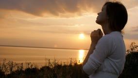 转向上帝的年轻美女本质上,女孩祈祷折叠了她的手在下巴,宗教的概念 股票视频