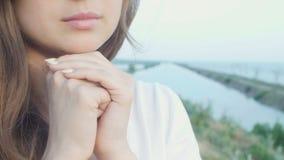 转向上帝的年轻美女本质上,女孩祈祷折叠了她的手在下巴,宗教的概念 影视素材