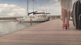 转回去运载重的行李走在木桥的适合的可爱的少妇在高跟鞋在游艇小船港口 股票录像