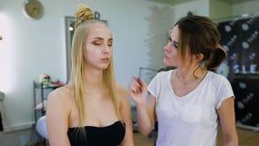 转换 在时髦美容院,一位专业化妆师图象为一个可爱的金发碧眼的女人做准备 股票录像