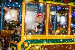 转盘的两个小孩男孩在圣诞节市场上 免版税库存照片