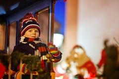 转盘的小孩男孩在圣诞节市场上 库存照片
